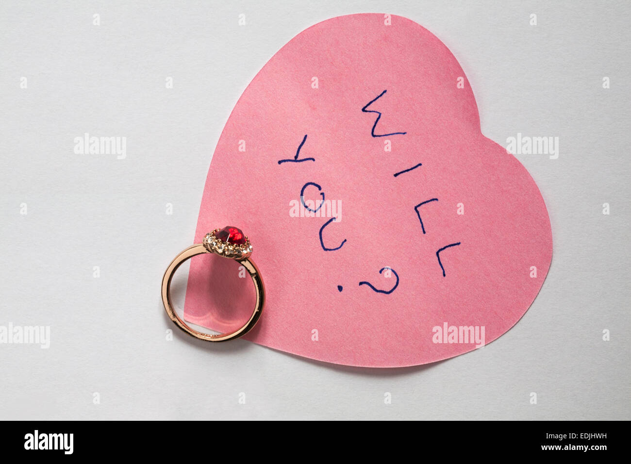 will you? message written on pink heart shaped post it note with engagement ring - marriage proposal isolated on - Stock Image