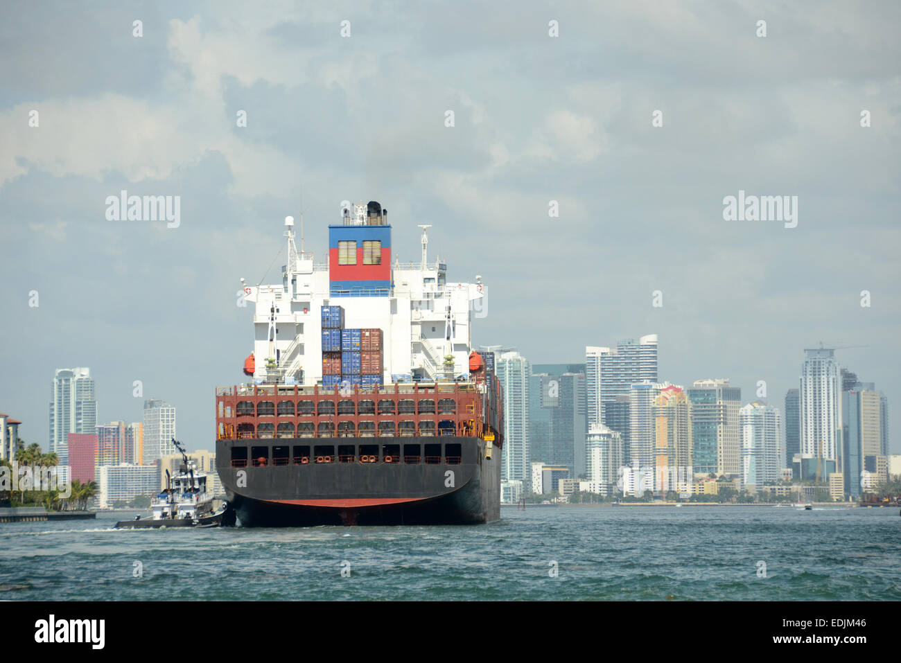Heavy container cargo ship enters the port of Miami, Florida - Stock Image