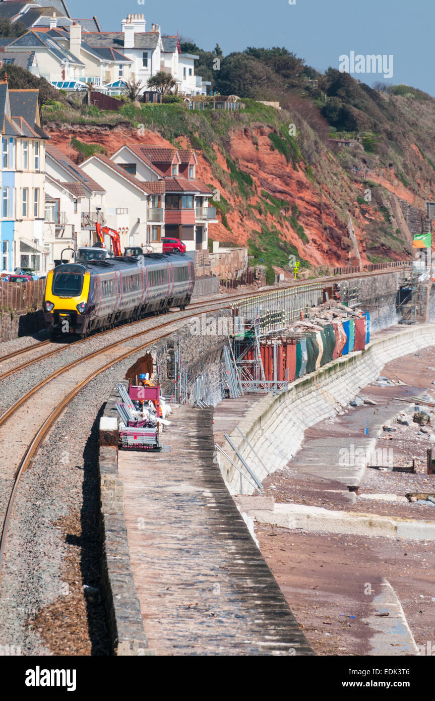 Cross Country Trains passenger train passing over the damaged section of seawall at Dawlish - Stock Image