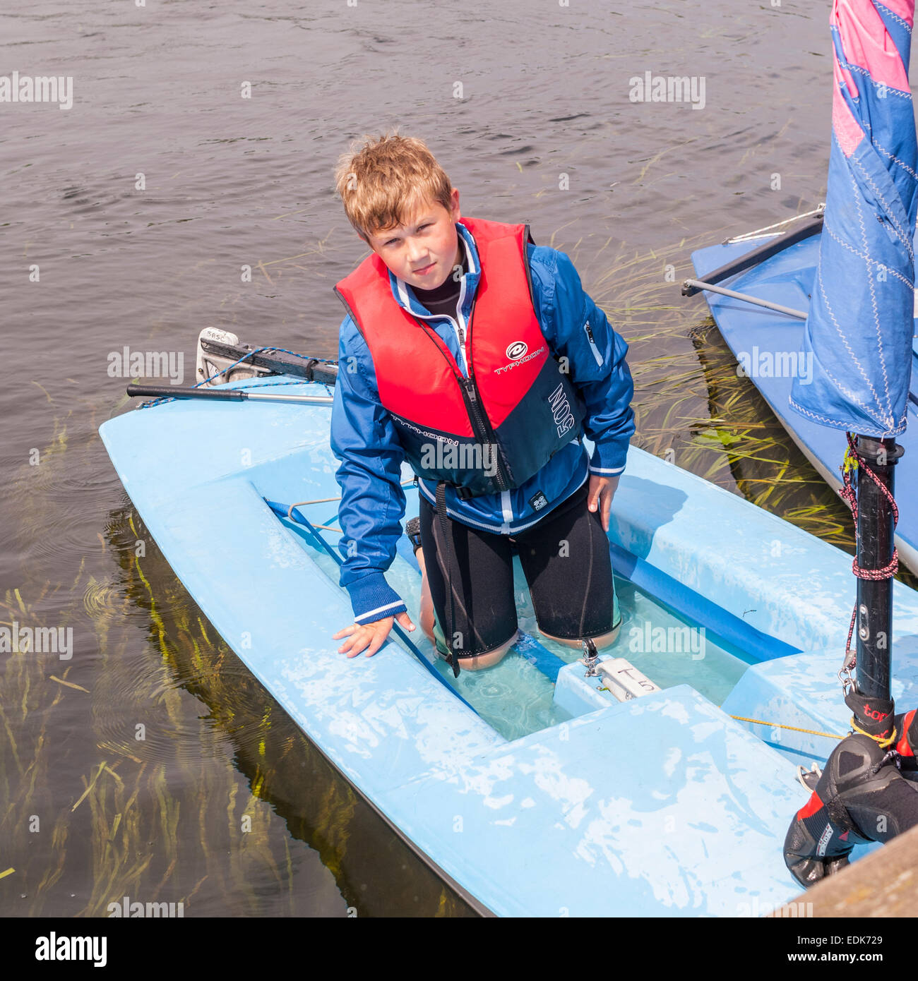 A 10 year old boy at Beccles Amateur sailing Club in Suffolk , England ,  Britain , Uk