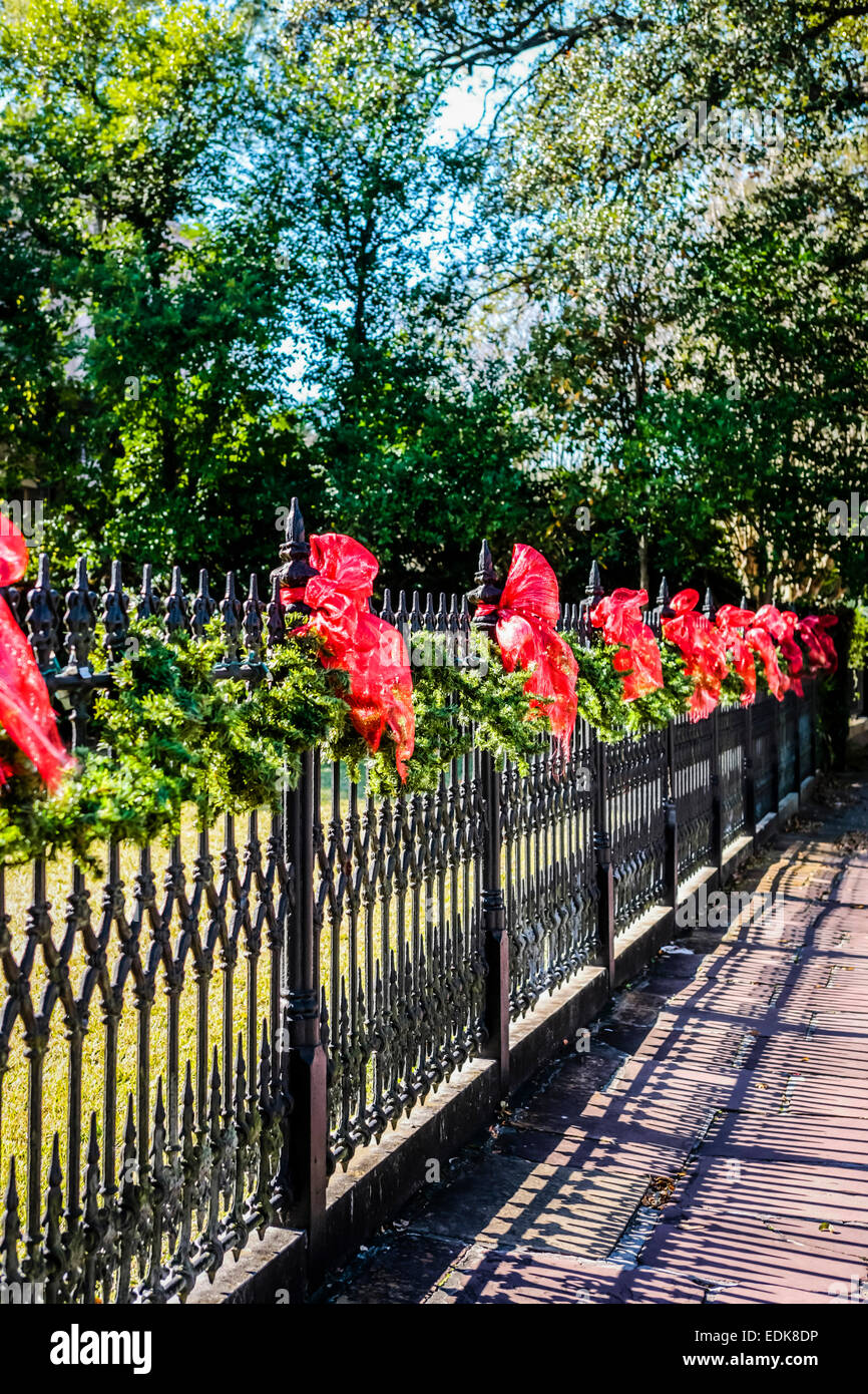 Red bows ties to a cast Iron ornate fence around a n estate in the Garden District of New Orleans LA - Stock Image