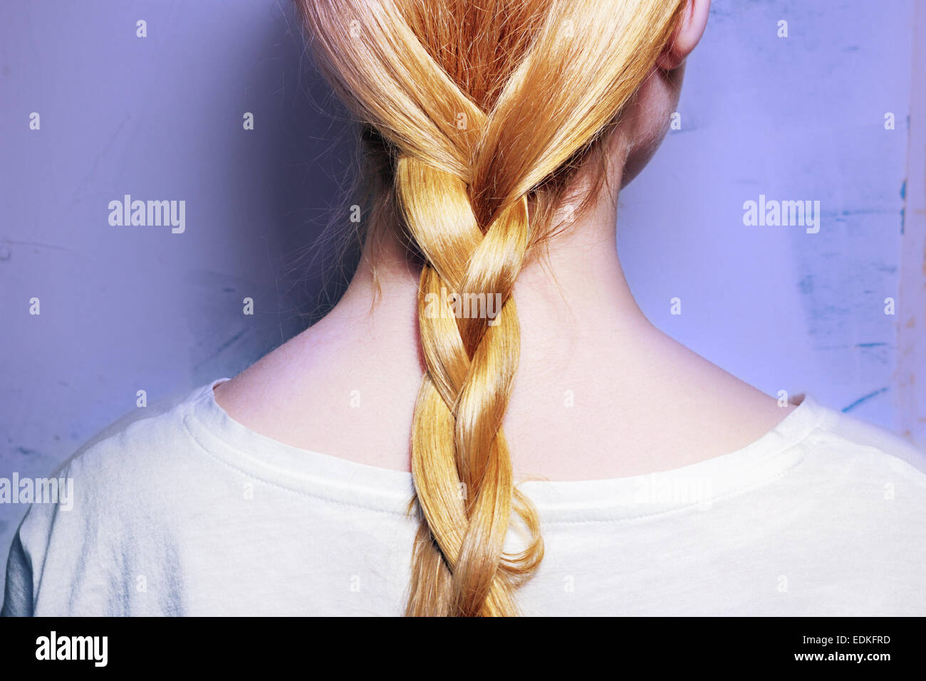 Girl with blond hair, braided into a braid on a purple background - Stock Image