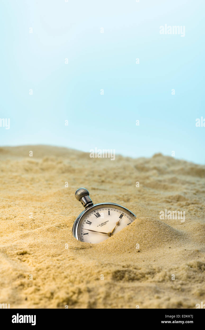 Pocket watch buried in a sandy beach. - Stock Image