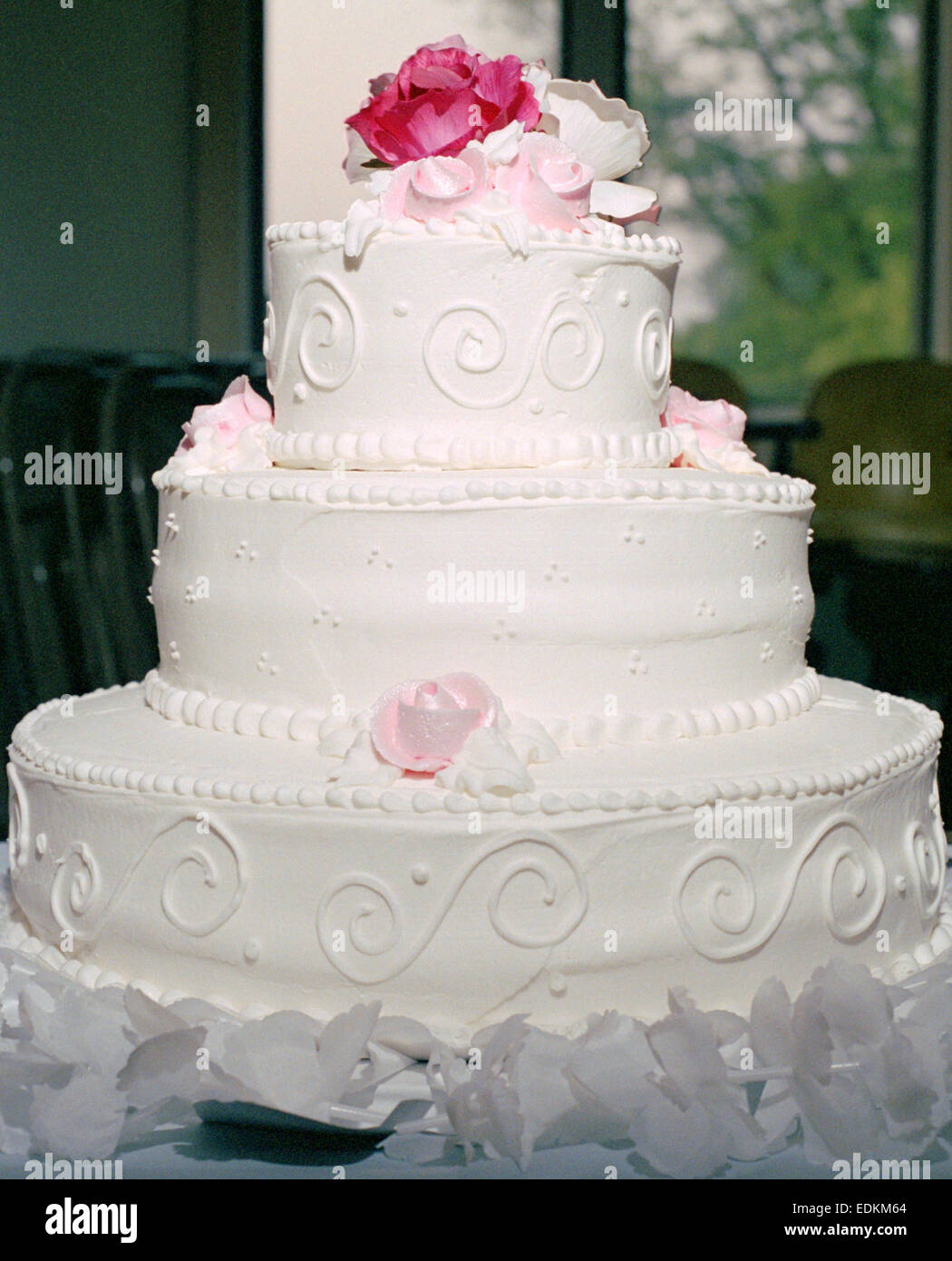 A 3 tier white wedding cake with pink roses Stock Photo: 77264940 ...