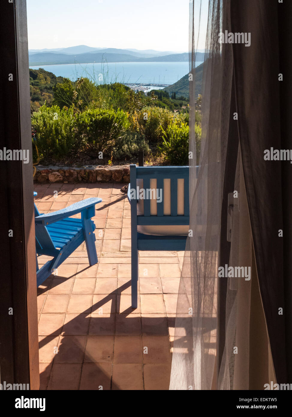 two blue wooden deckchairs on the patio of a villa on the sea views from inside - Stock Image
