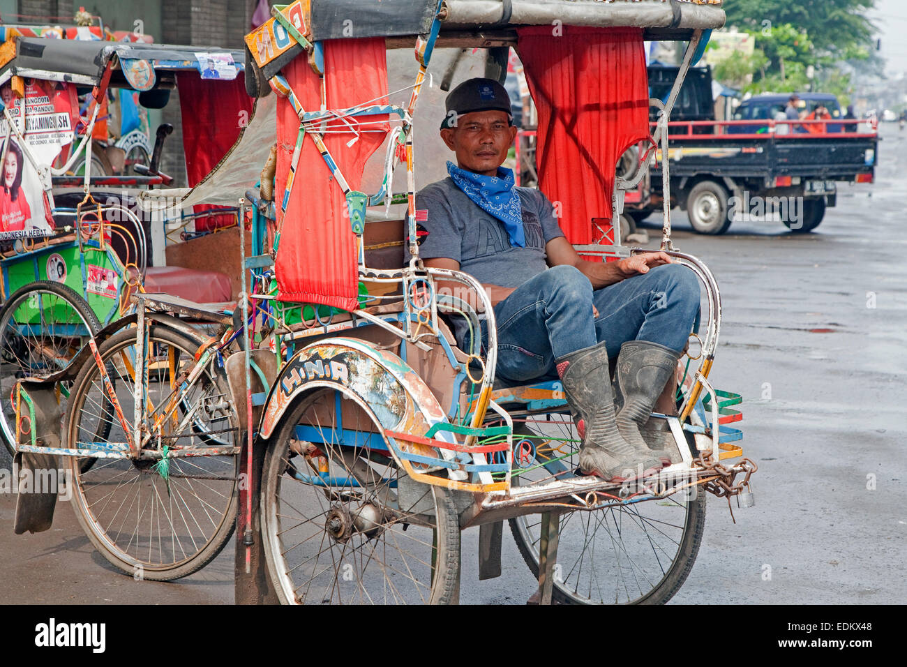 Indonesian becak driver waiting for clients in his cycle rickshaw, Kota Bandung, West Java, Indonesia - Stock Image