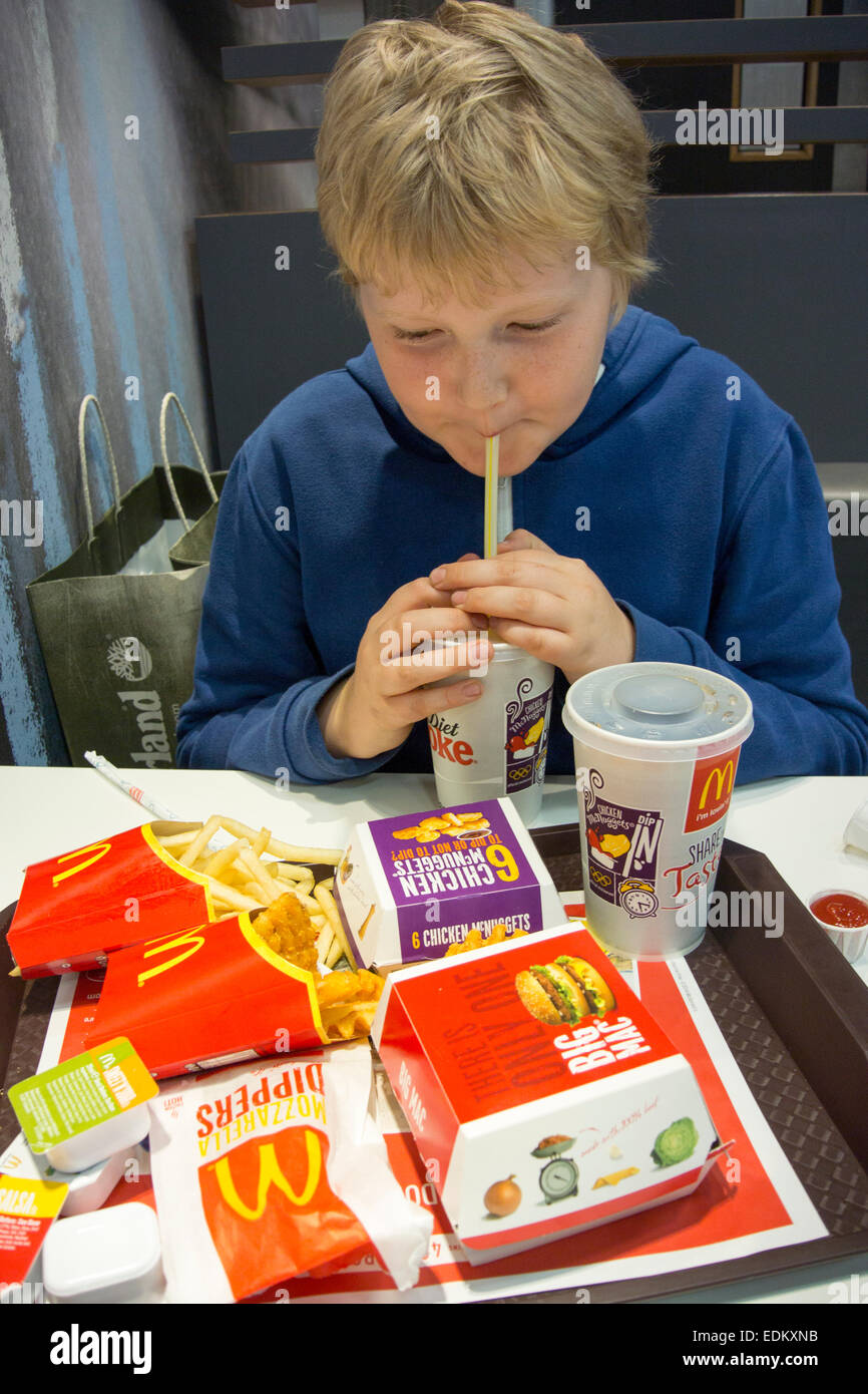 Young boy eating at a fast food resturant, UK. - Stock Image