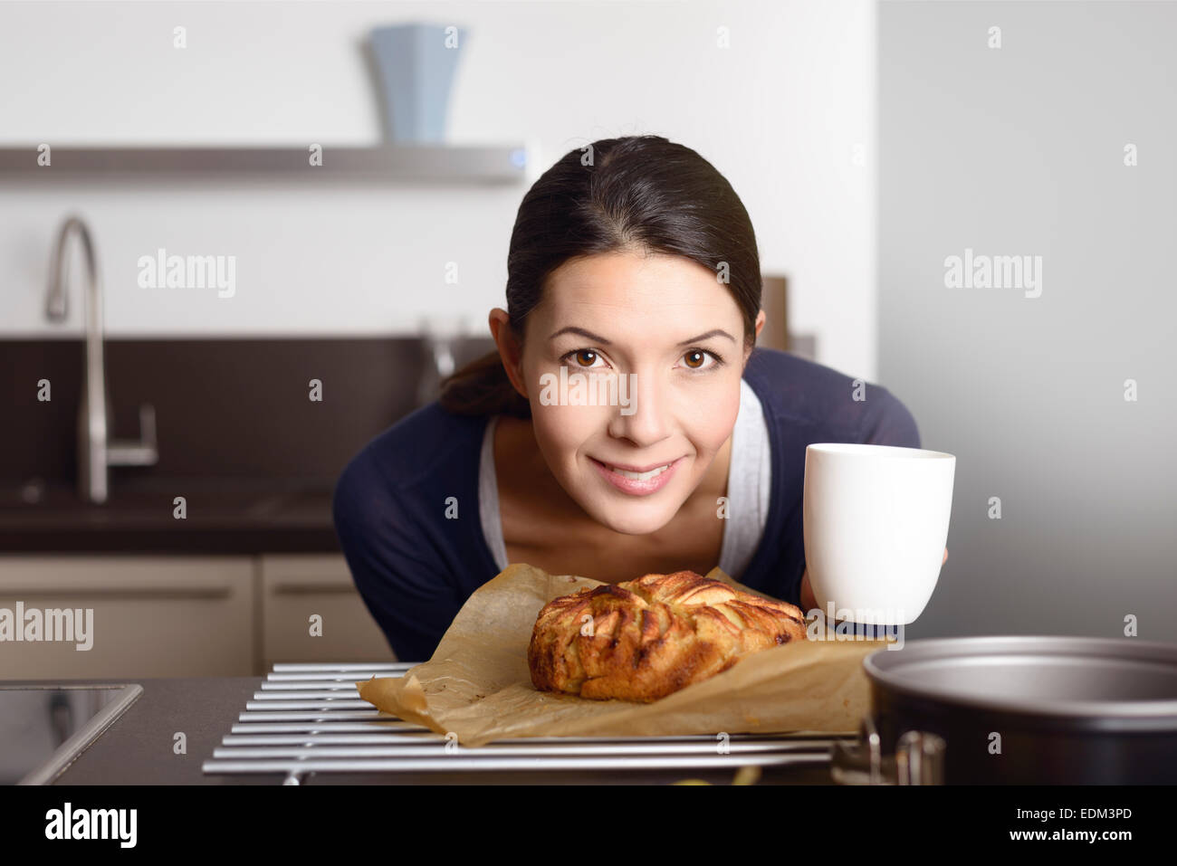Proud attractive young cook bending down to a freshly baked apple cake while looking at the camera with a happy - Stock Image