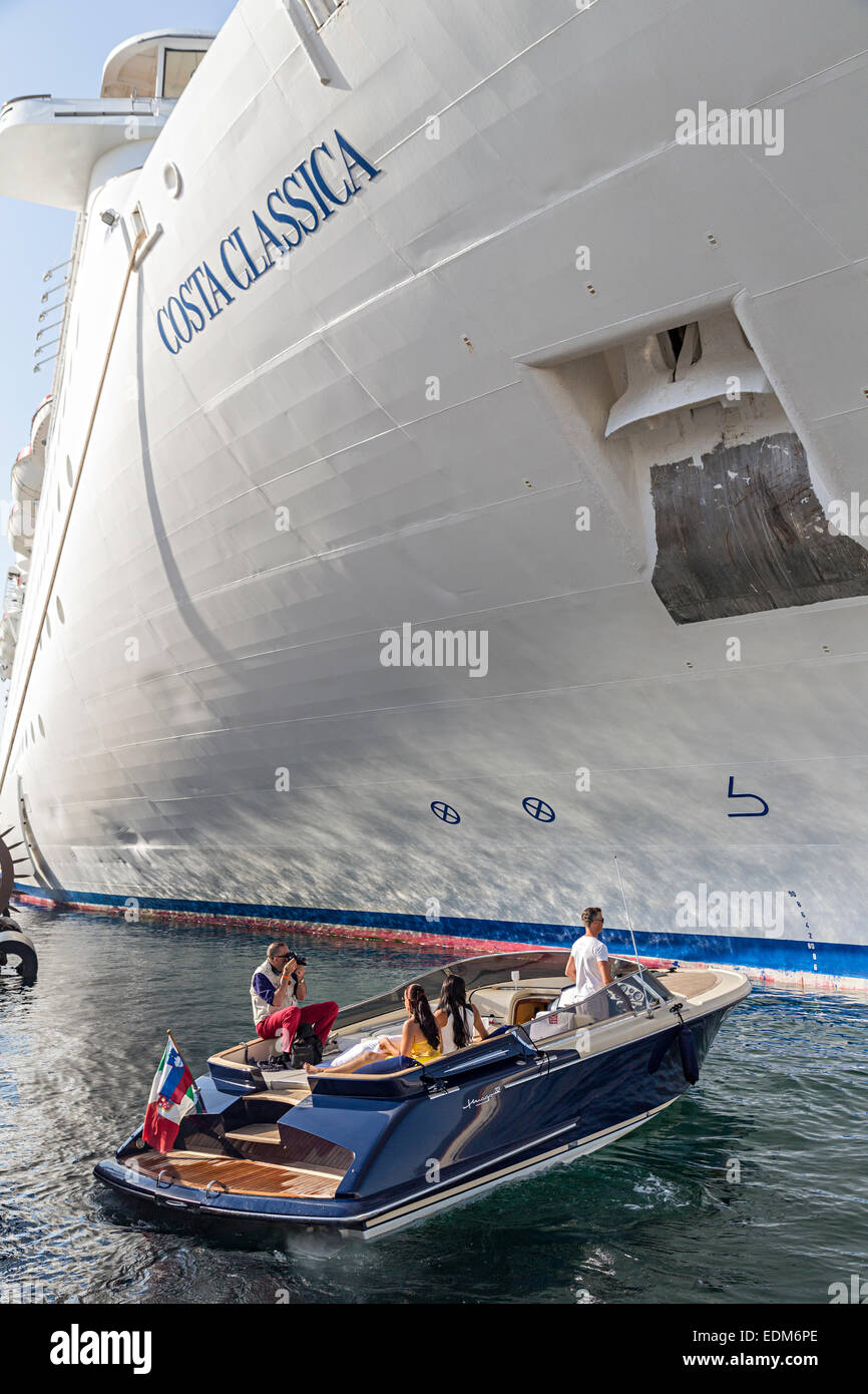 Costa Classica cruise ship moored in Trieste harbout with motor launch by prow, Italy - Stock Image