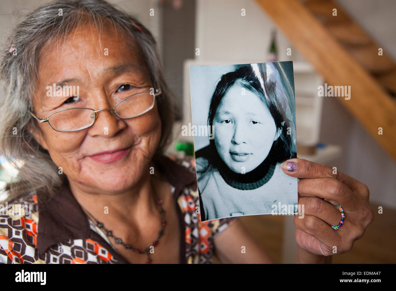 Local woman in Greenland holding up a portrait of herself. - Stock Image