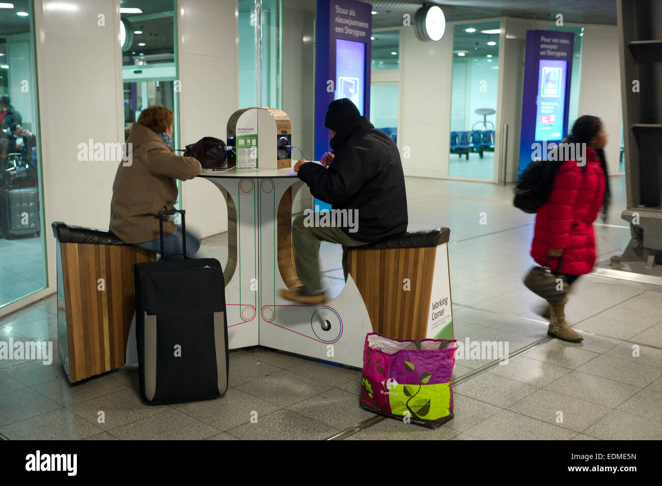 The 'Working Corner' in Brussels Train station. People are able to charge and run  mobile phones and laptops - Stock Image