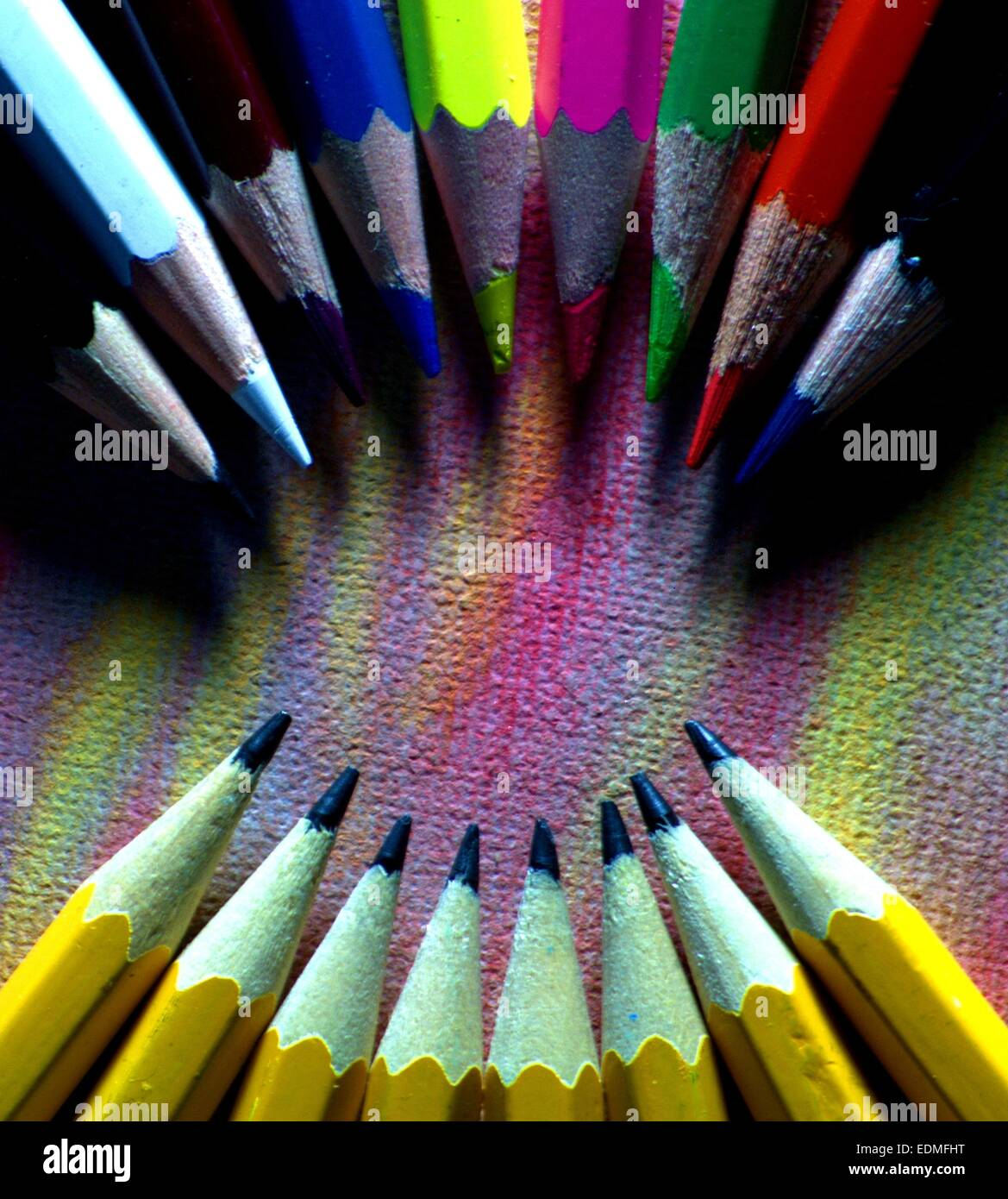 colored pencils in an arc formation facing an arc of regular pencils - Stock Image