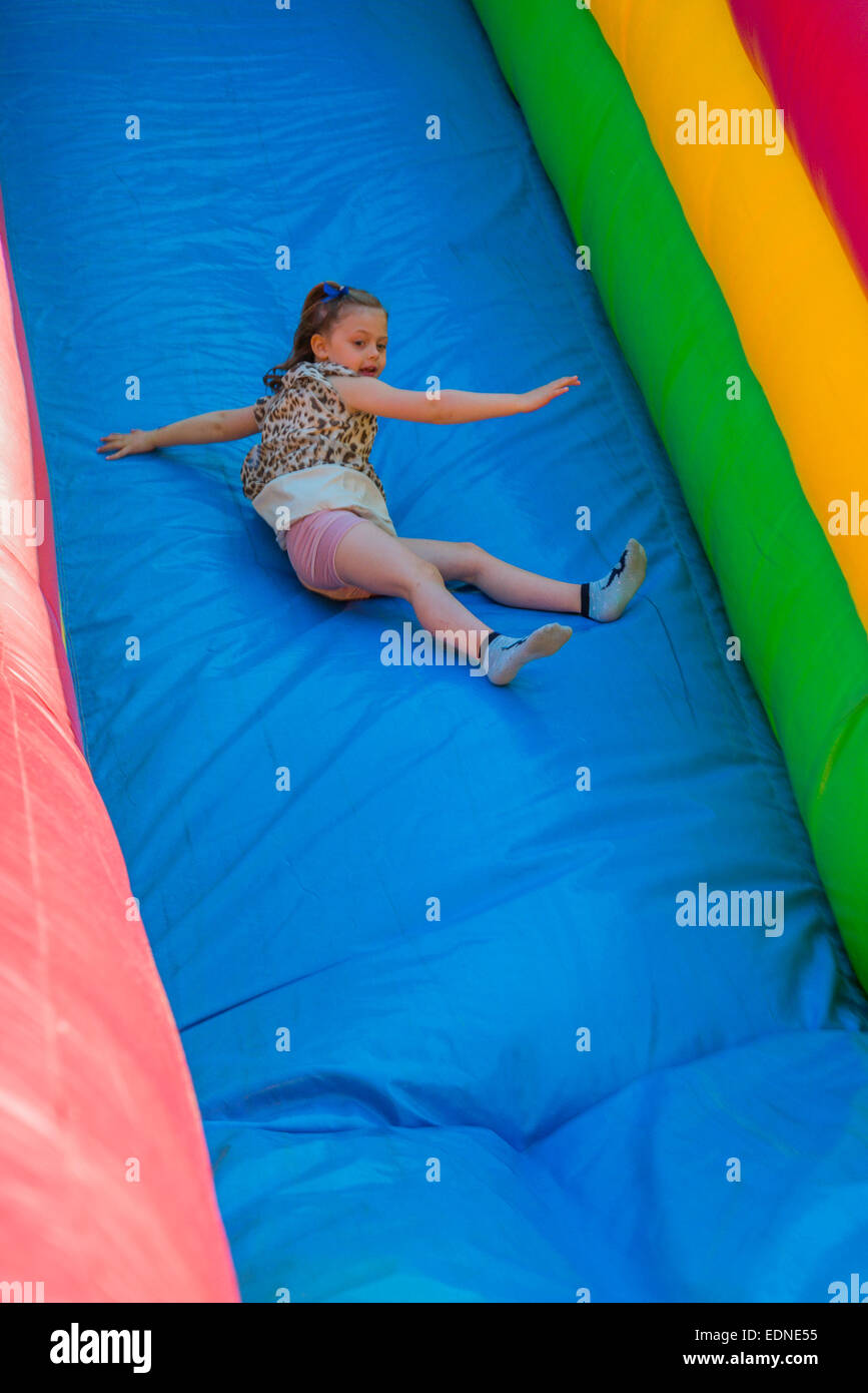 Girl enjoys inflatable slide attraction at Spring Fair. - Stock Image
