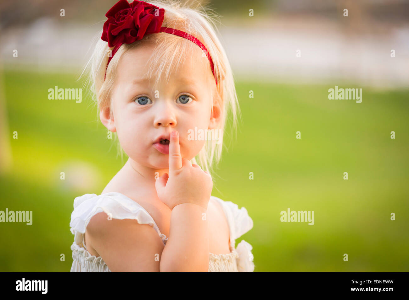 Beautiful Adorable Little Girl With Her Finger on Her Mouth Wearing White Dress In A Grass Field. Stock Photo