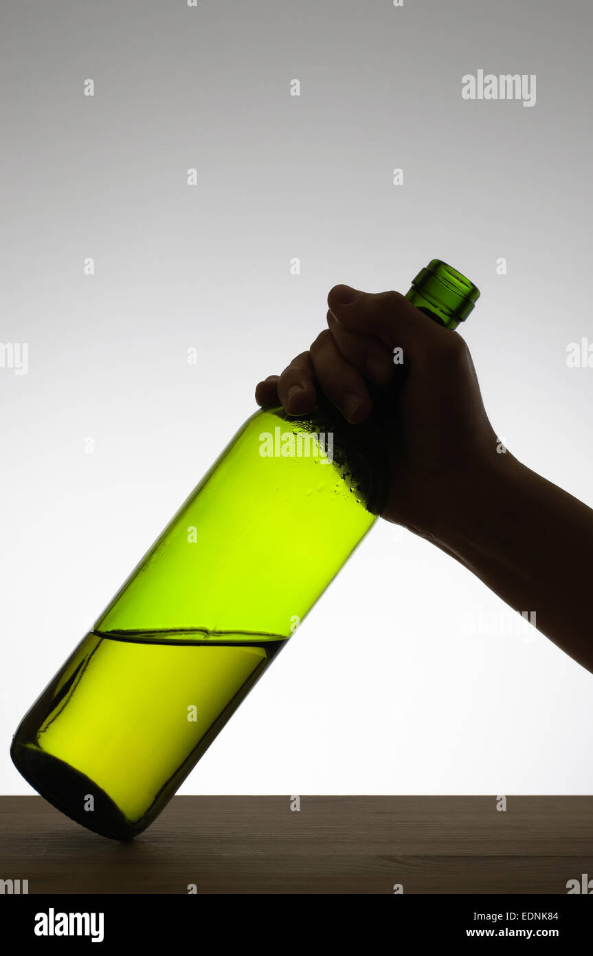 Silhouette of a hand grabbing a green wine bottle - Stock Image
