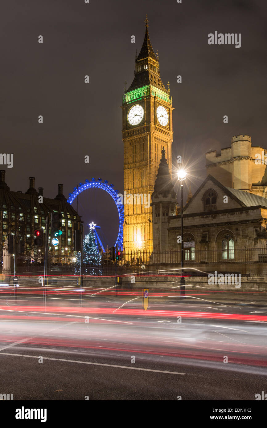 The Houses of parliament,Big Ben and the London Eye at night with traffic streaks. - Stock Image