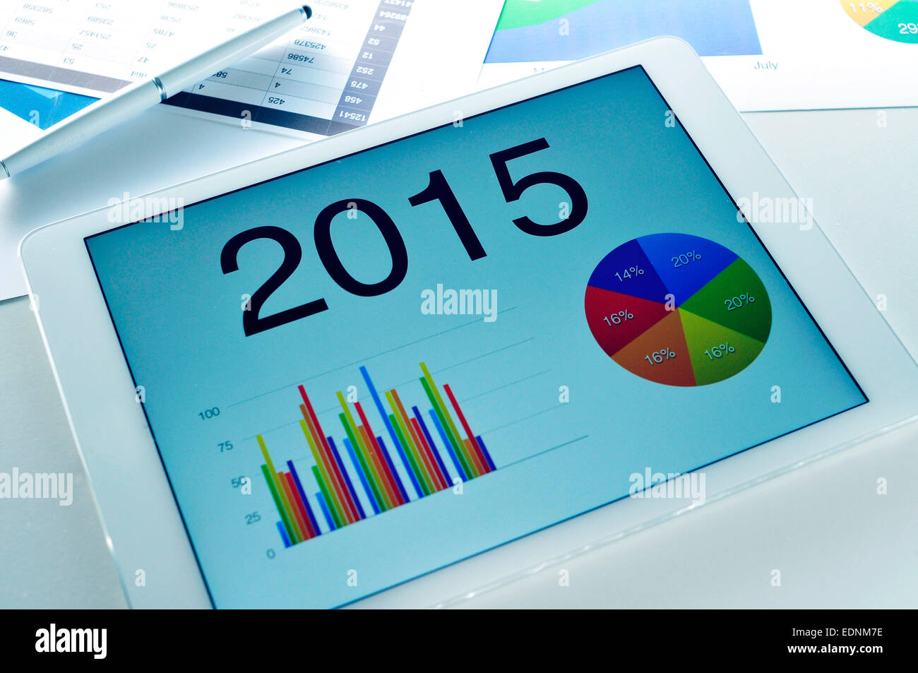 different charts with the economic forecast for 2015 in a tablet, on a desk full of charts - Stock Image