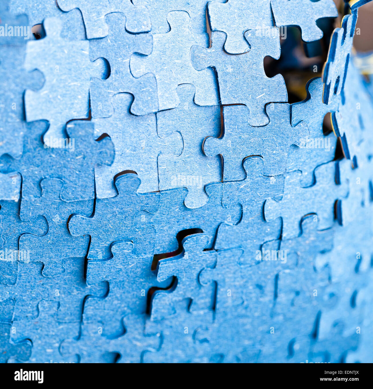 Real photograph of the backside of blue puzzle jigsaw in available light. - Stock Image