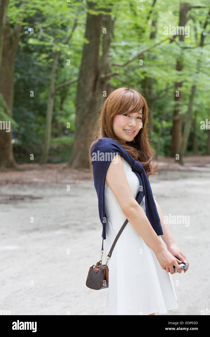 A woman in a Kyoto park posing for a photograph. - Stock Image