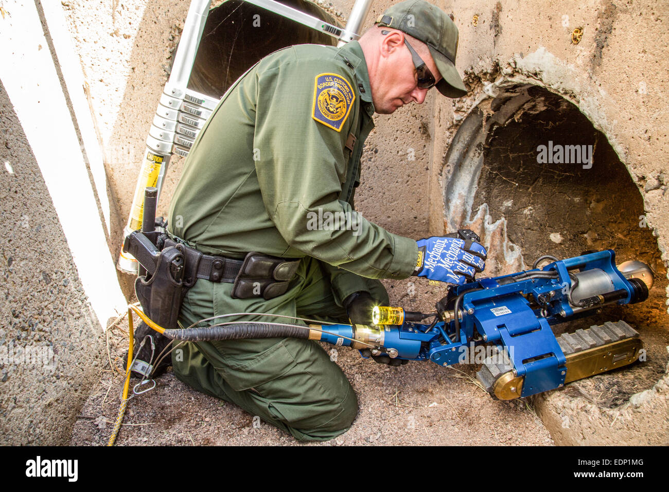US Customs and Border Protection Officers operate a Versatrax 150 pipe inspection robot. See description for more - Stock Image