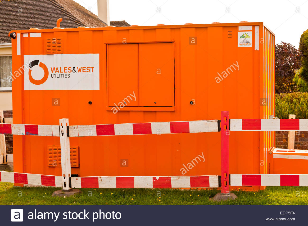 Modern version of the 'workman's hut' for Wales & West Utilities surrounded by barriers on grass - Stock Image