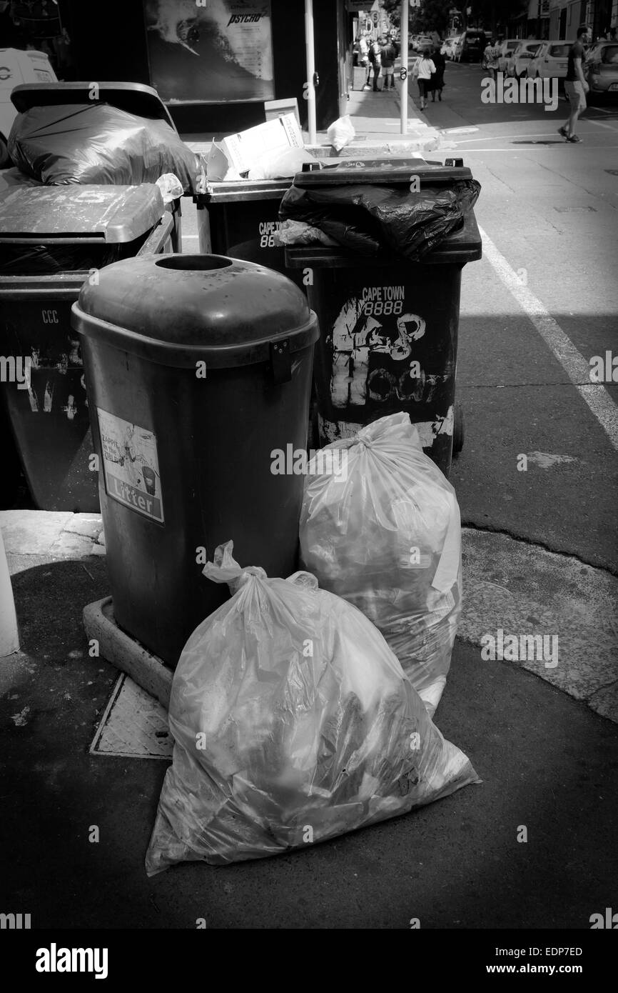Rubbish bags and refuse wheelie bins on pavement in street in Cape Town city center . (Black and white photograph) - Stock Image