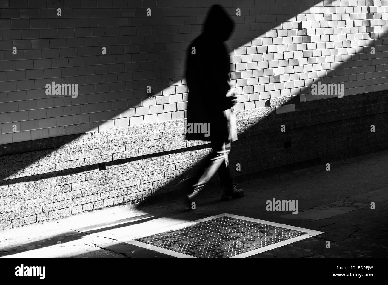 hooded figure in shadow with tiles - Stock Image