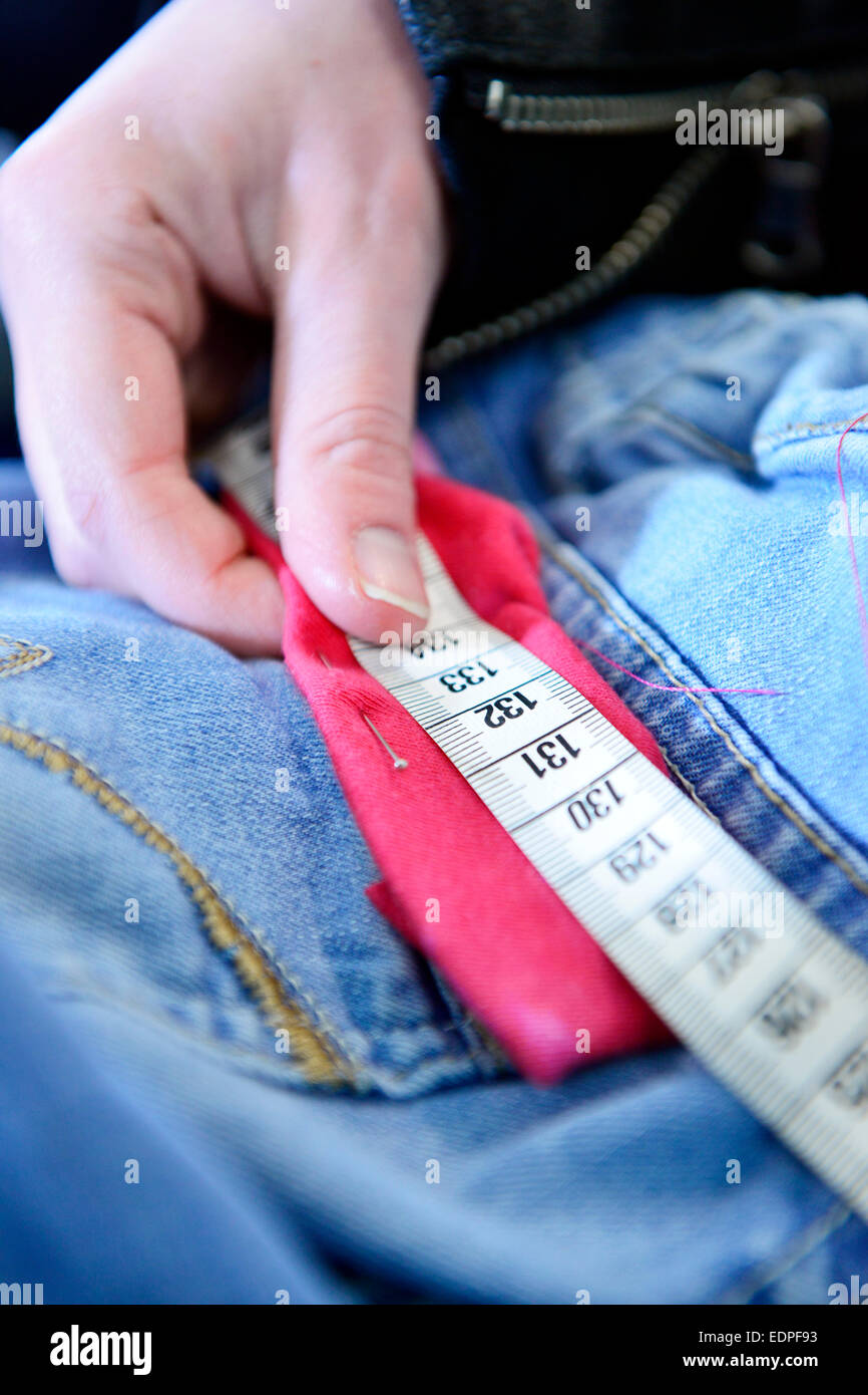 Tailor measuring a n adjusting garments - Stock Image