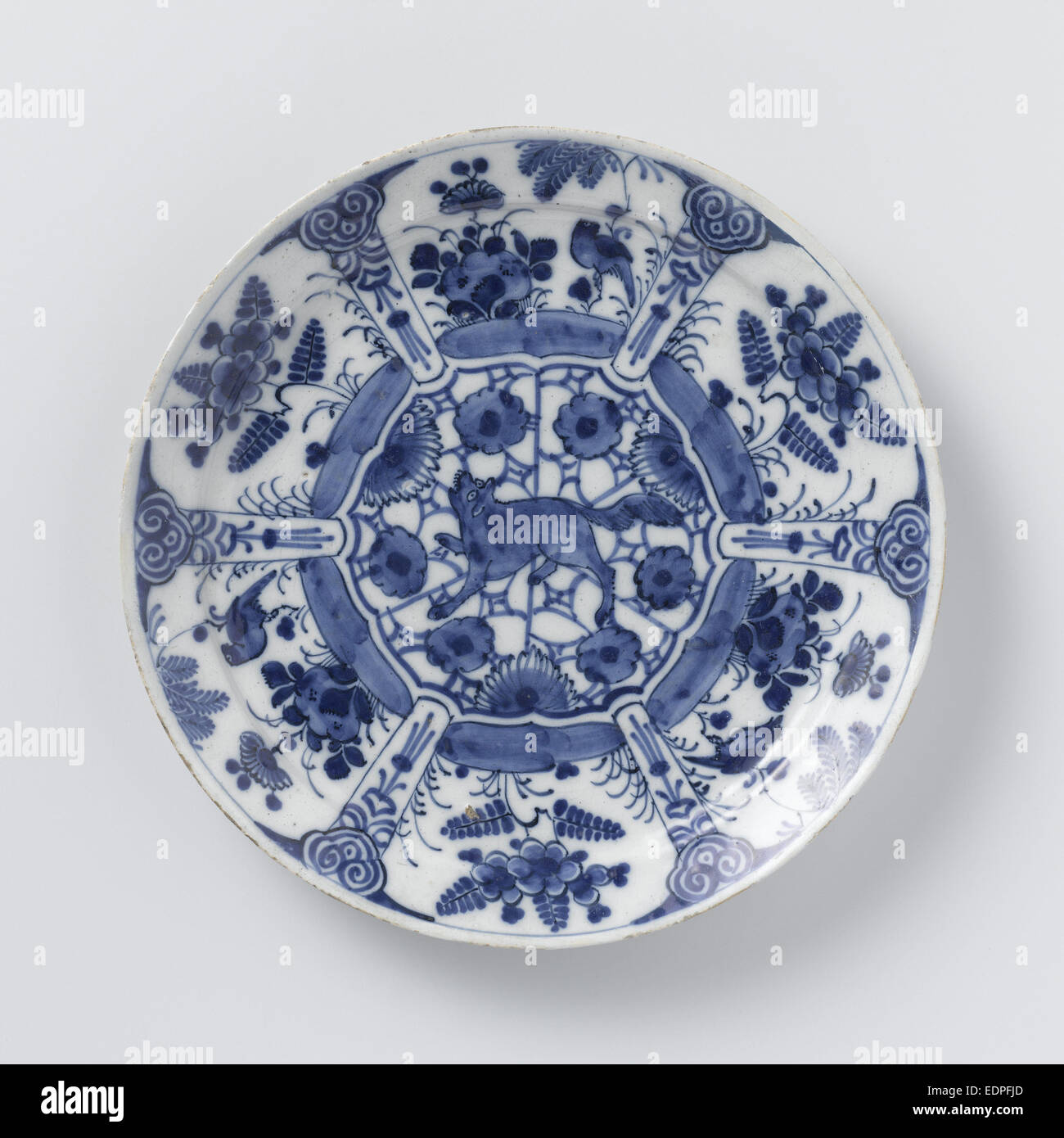 Blue and white Delft pottery, decorated with plants and birds and a growling wolf or fox in the middle - Stock Image