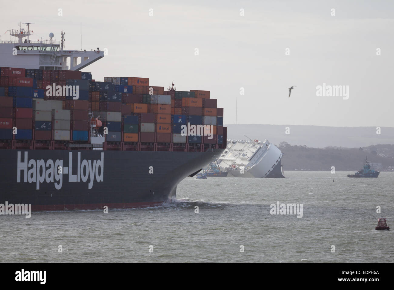 The Hapag-Lloyds cargo ship, Essen Express departing Southampton, about to pass the stricken ship, Hoegh Osaka in - Stock Image