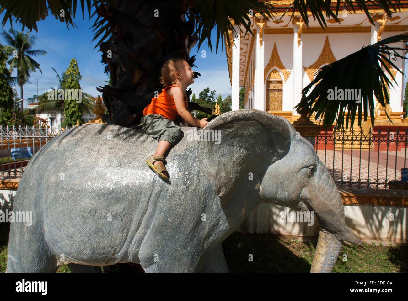Girls uploaded an elephant statue in Wat Kampheng Temple. Battambang. Cambodia. Travel with children's. Wat - Stock Image