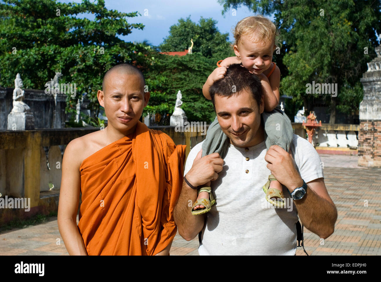 Family with a monk in a Buddhist temple Wat Kandal Battambang. Cambodia. Travel with children's. Father traveling - Stock Image