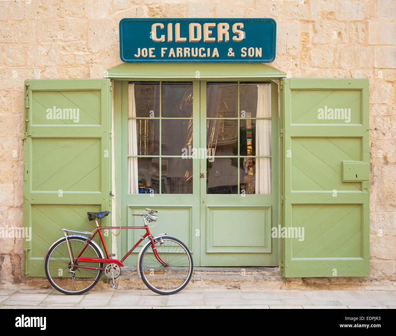 Retro Red Bicycle outside Green doors of traditional Gilders shop Mdina Malta EU Europe - Stock Image