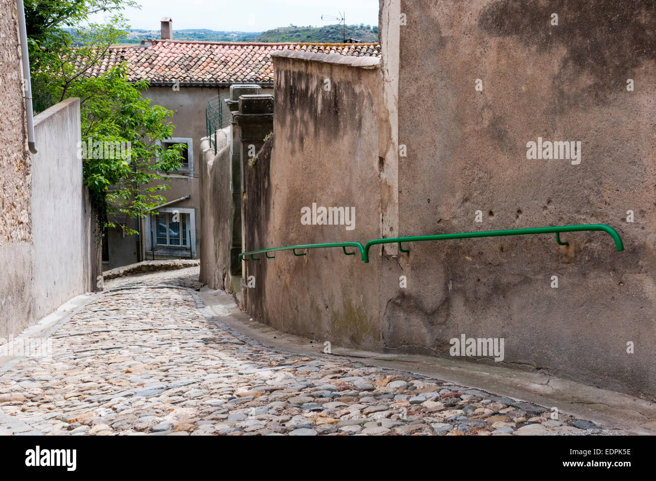 A steep cobbled street with a handrail in the small village of Puissalicon, Languedoc, France.  An historic circulade - Stock Image