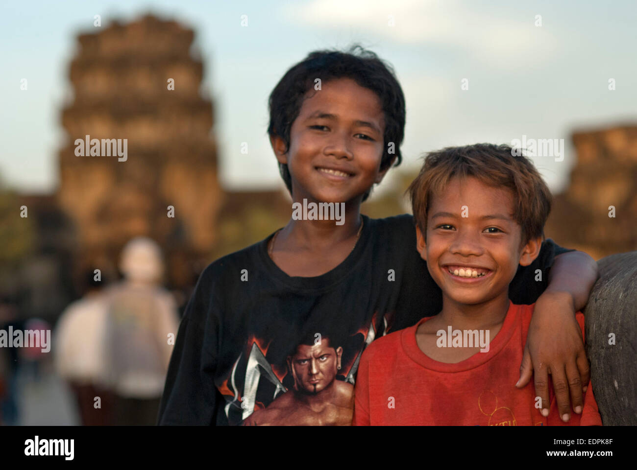Portrait of two boys in front of the faces of the Bayon temple. Angkor Thom. We stand before it stunned. It is like Stock Photo