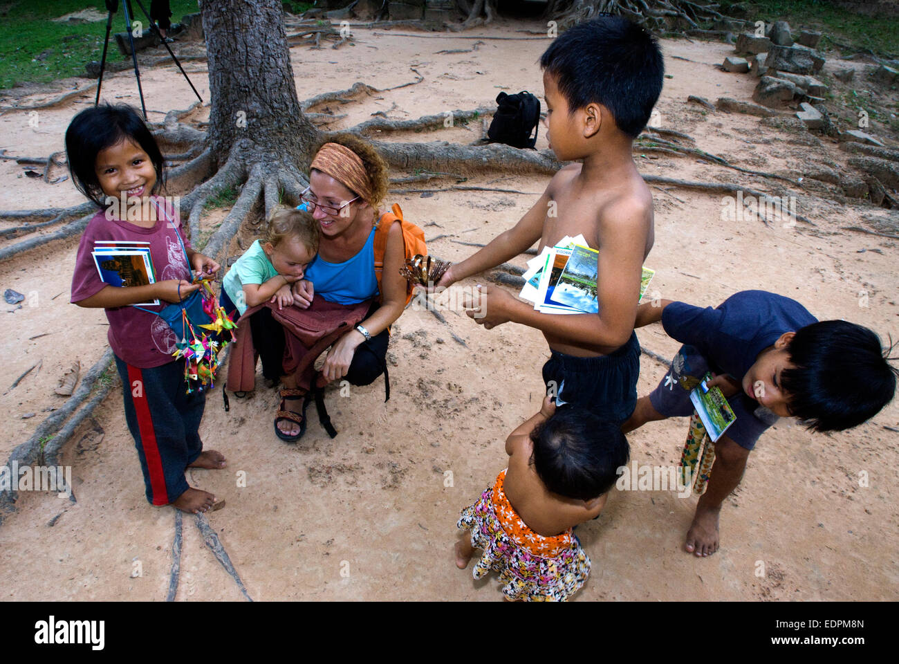 Travel with children's. Boys selling postcards and souvenirs to a mother walking with her daughter. Ta Som Temple. - Stock Image