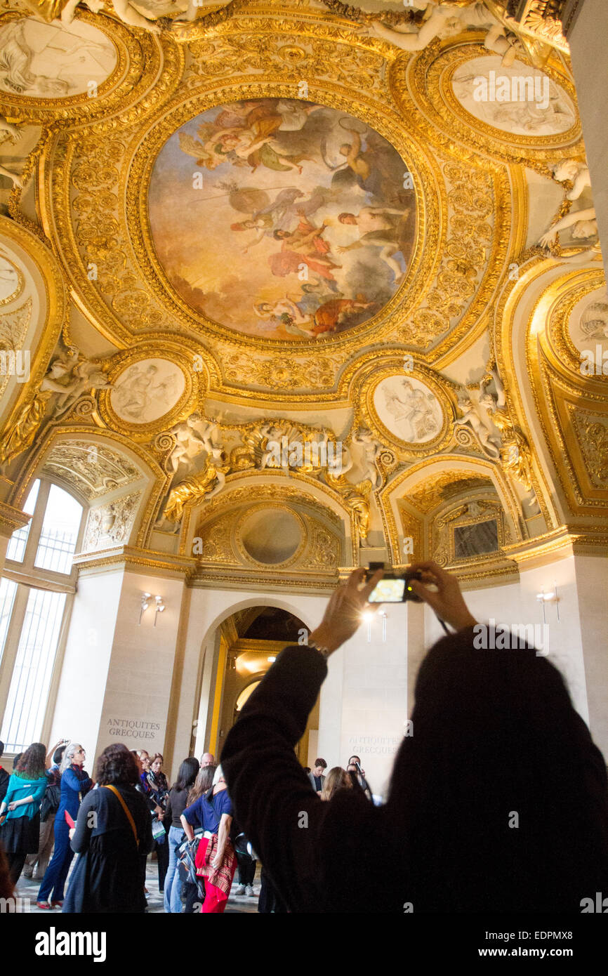 Tourist taking photos in Louvre Museum, Paris, France - Stock Image