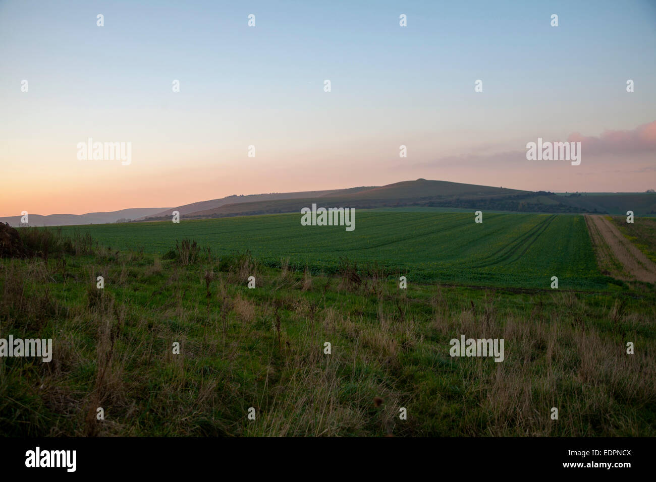 Chalk downland landscape at dusk with red sky from setting sun view to Milk HiIl, Alton Barnes, Wiltshire, England, - Stock Image