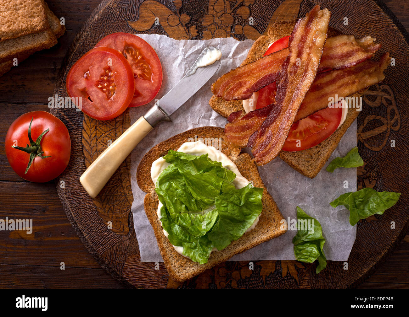 A delicious BLT bacon, lettuce, and tomato sandwich on rustic tabletop. - Stock Image