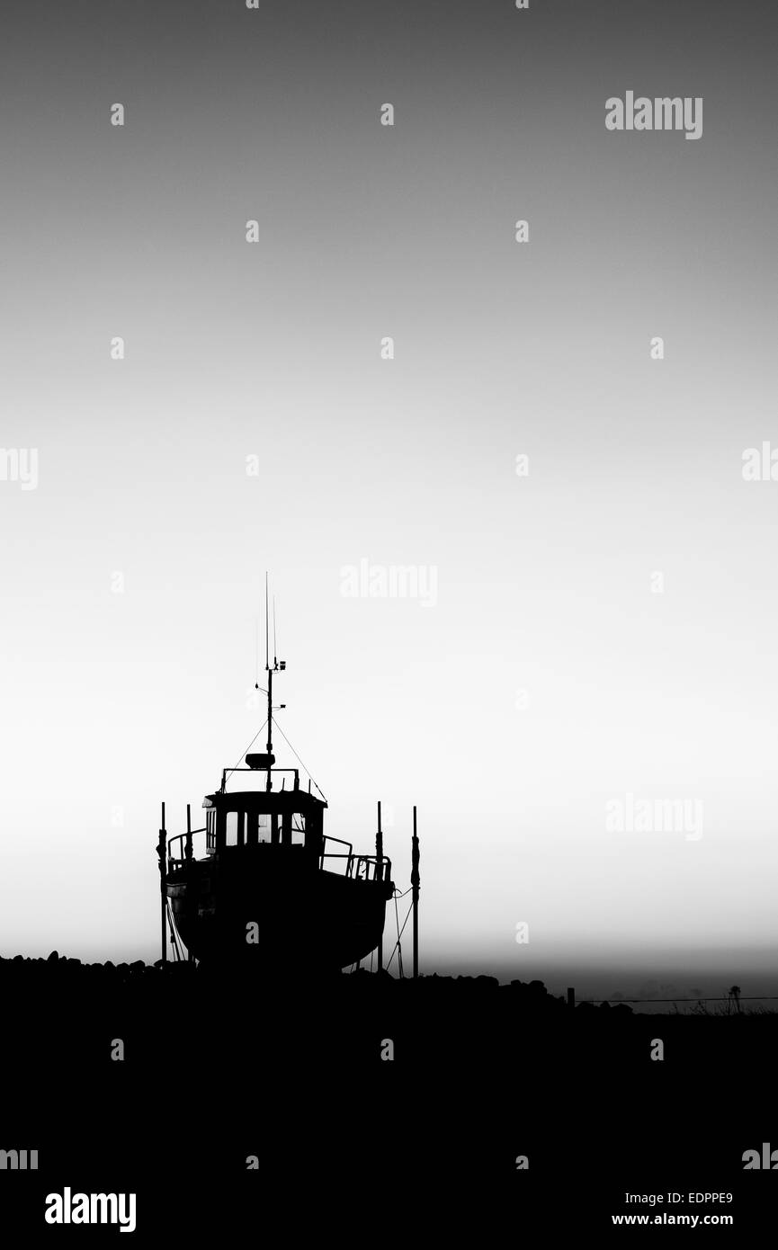 Fishing boat on dry land at sunrise in the harbour at Lindisfarne, Holy Island, Northumberland, England. Silhouette. - Stock Image