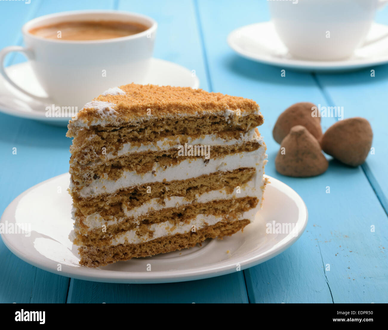 piece of cake on blue wooden table in the background cup of coffee and chocolate truffles - Stock Image