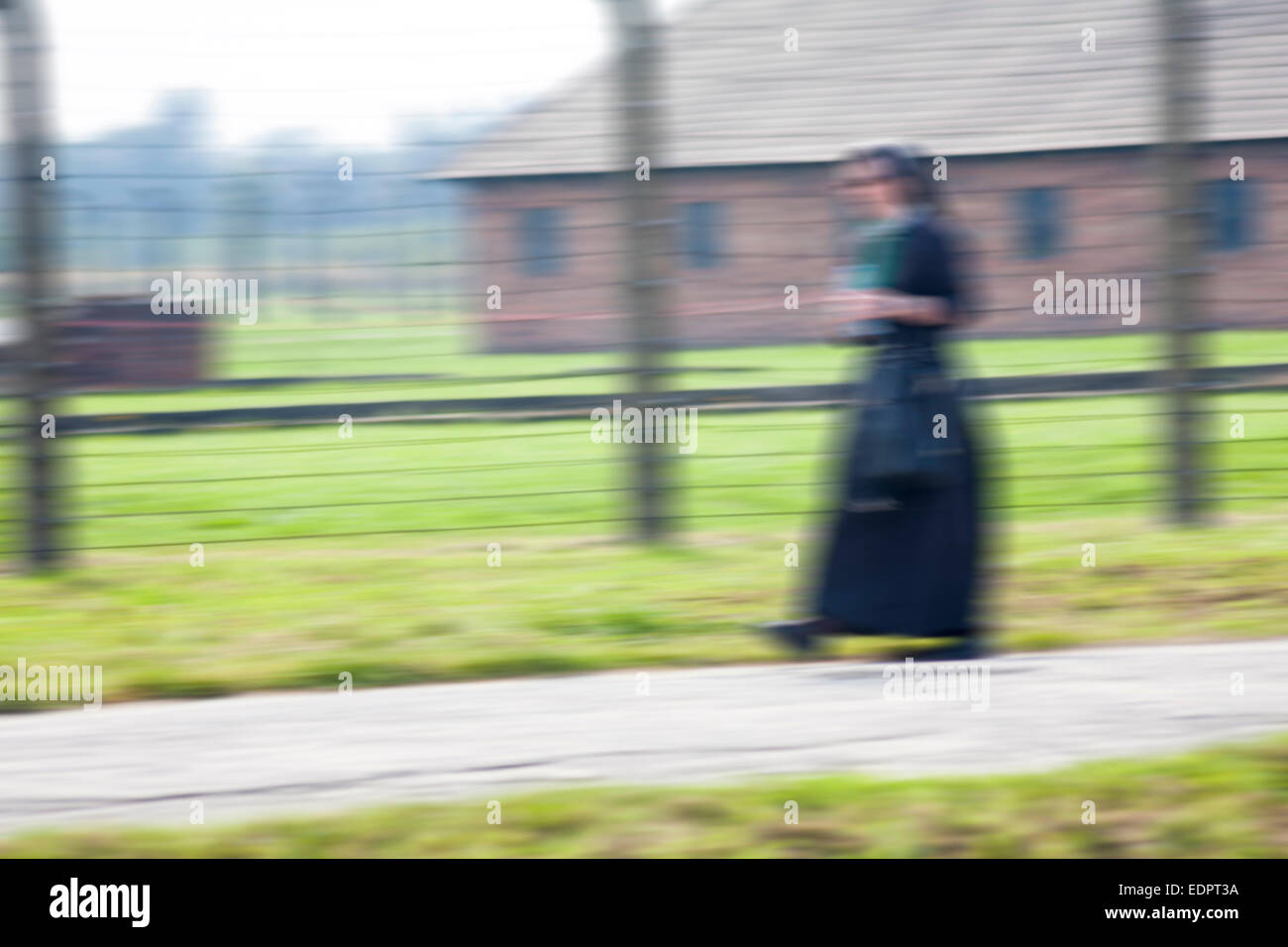 Nun hurrying past barbed wire fence and blocks at the Auschwitz-Birkenau concentration camp, Auschwitz, Poland - Stock Image