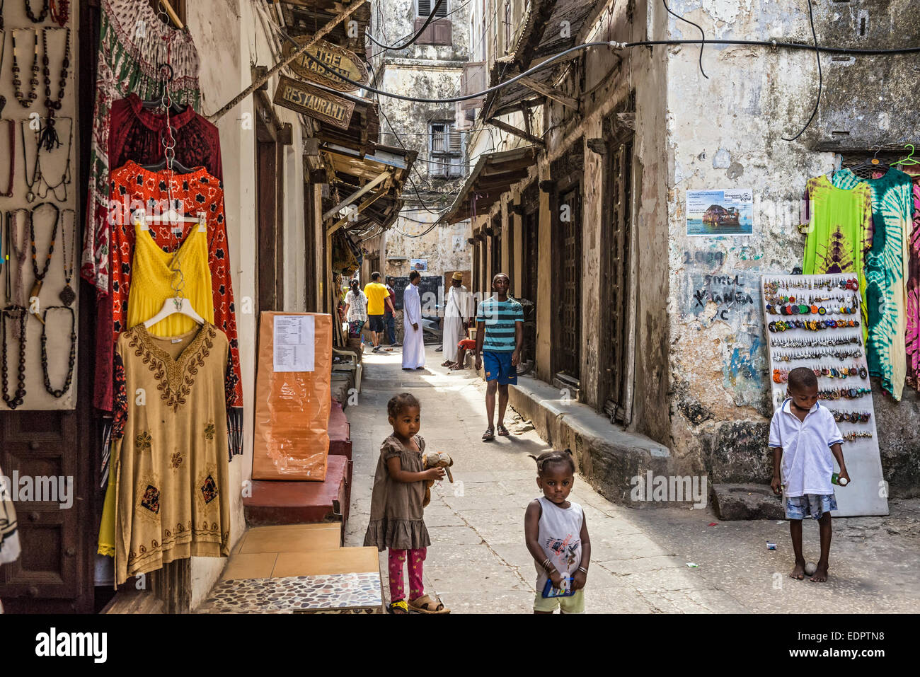 Local people on a typical narrow street in Stone Town, Zanzibar - Stock Image