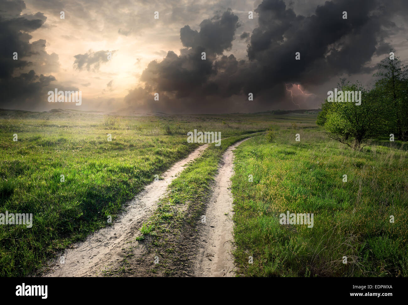 Lightning and storm clouds over country road - Stock Image