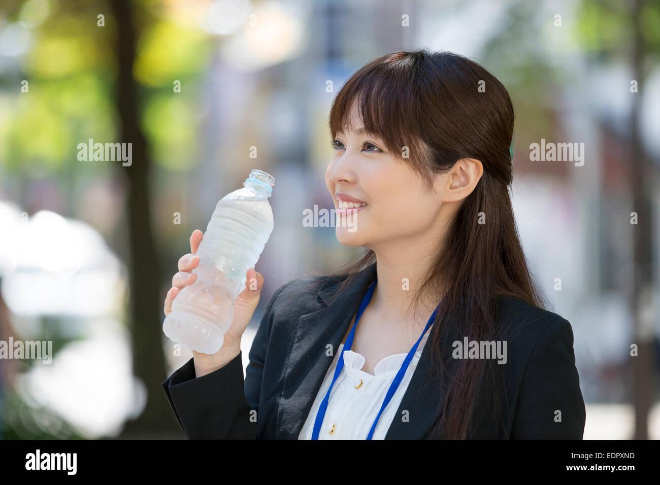 Smiling Businesswoman Holding Bottled Water - Stock Image