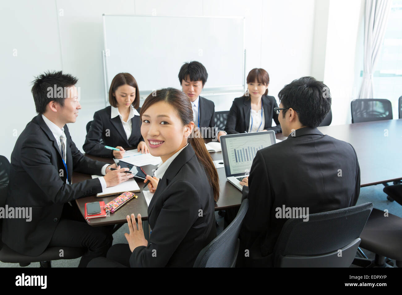 Business People in Meeting and A Woman Looking Back - Stock Image