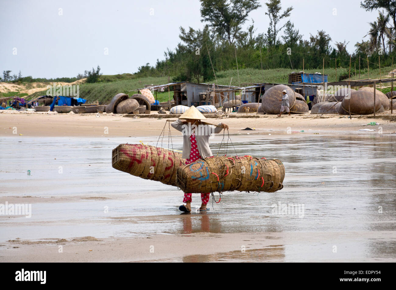Female fisherman balancing baskets at beach in south vietnam Mui Ne - Stock Image
