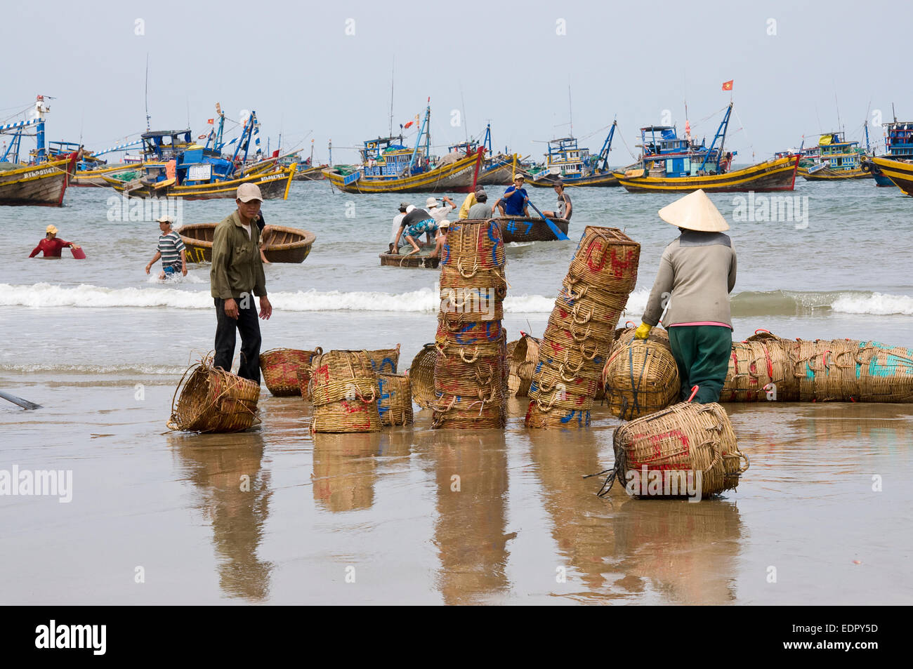 working fisherman stacking baskets at beach in south vietnam Mui Ne - Stock Image