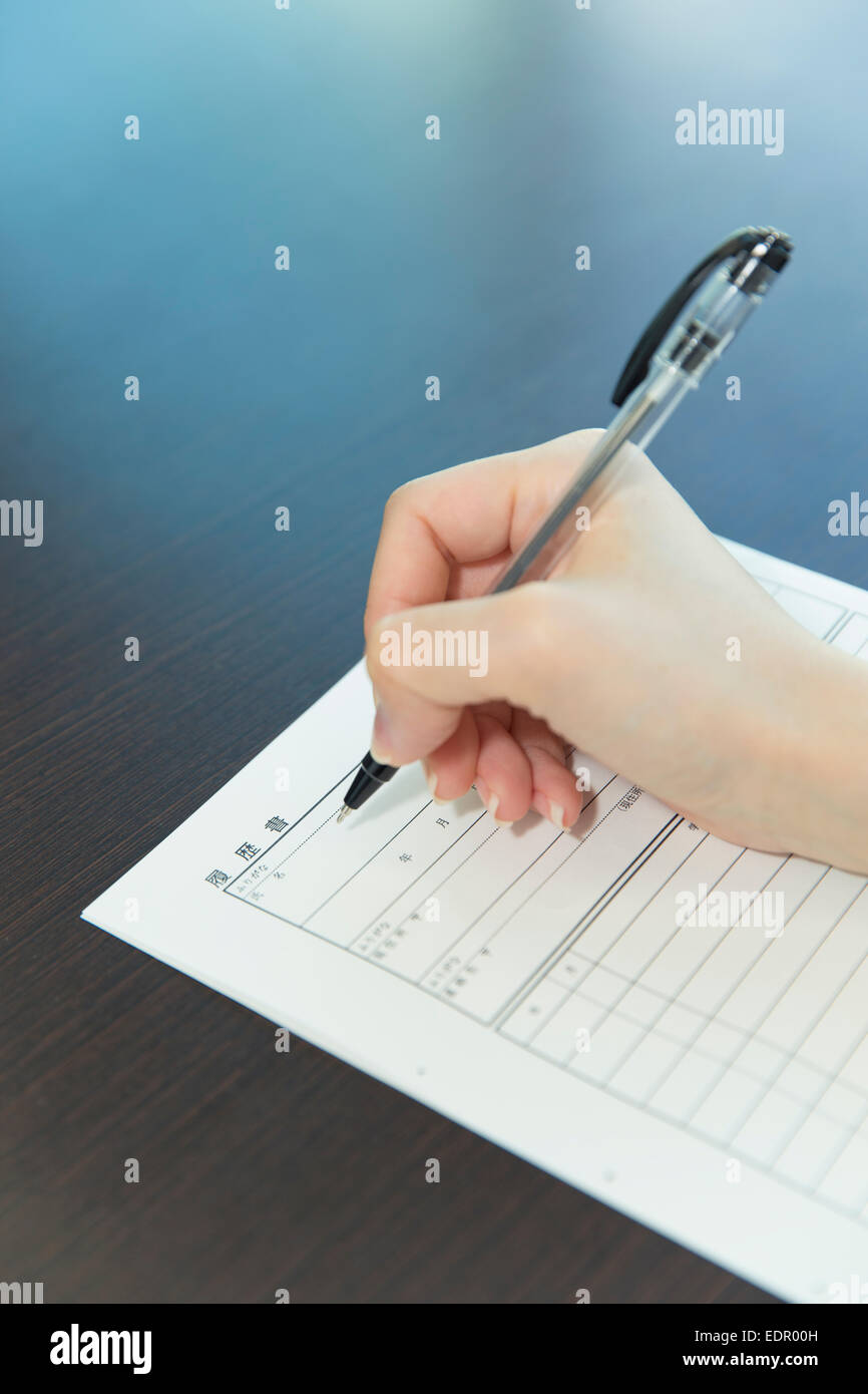 Woman Hand with Pen Filling out Job Application - Stock Image