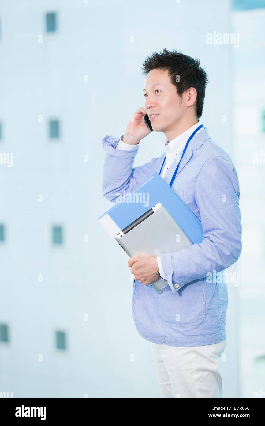 Businessman Holding File and Talking on Mobile Phone - Stock Image
